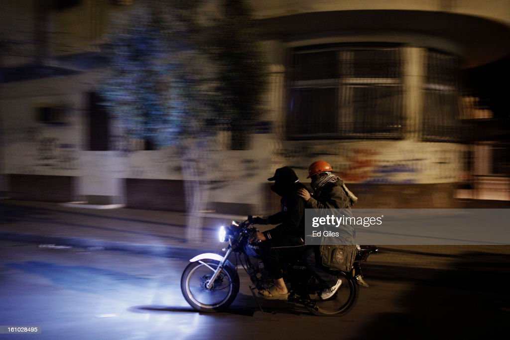An injured protester is carried away on a motorcyle after suffering from exposure to tear gas fired by Egyptian riot police during violent protests near the Presidential Palace in Heliopolis on February 8, 2013, in Cairo, Egypt. Protests continued across Egypt against President Morsi and the Muslim Brotherhood two weeks after the second anniversary of the Egyptian Revolution that overthrew former President Hosni Mubarak on January 25, 2011.(Photo by Ed Giles/Getty Images).