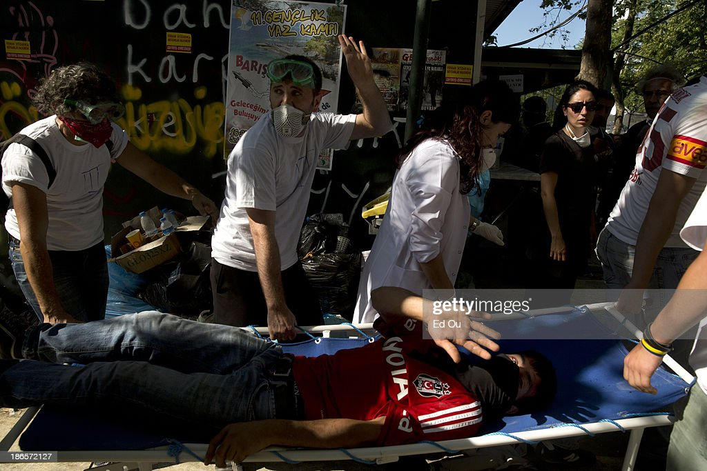 An injured protester is carried away on a stretched by medics during a clash with police in Istanbul Turkey on June 11 2013 A large force of riot...