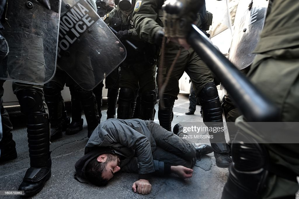 An injured protester lays on the street outside the Labour Ministry in Athens on January 30, 2013. Police were called in on Wednesday to dislodge around 30 Communist unionists from the labour ministry in a protest against new pension cut plans. The unionists were arrested and police used tear gas outside the building to disperse a larger group of protesters demanding their release.
