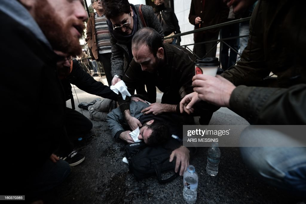 An injured protester receives treatment outside the Labour Ministry in Athens on January 30, 2013. Police were called in on Wednesday to dislodge around 30 Communist unionists from the labour ministry in a protest against new pension cut plans. The unionists were arrested and police used tear gas outside the building to disperse a larger group of protesters demanding their release.