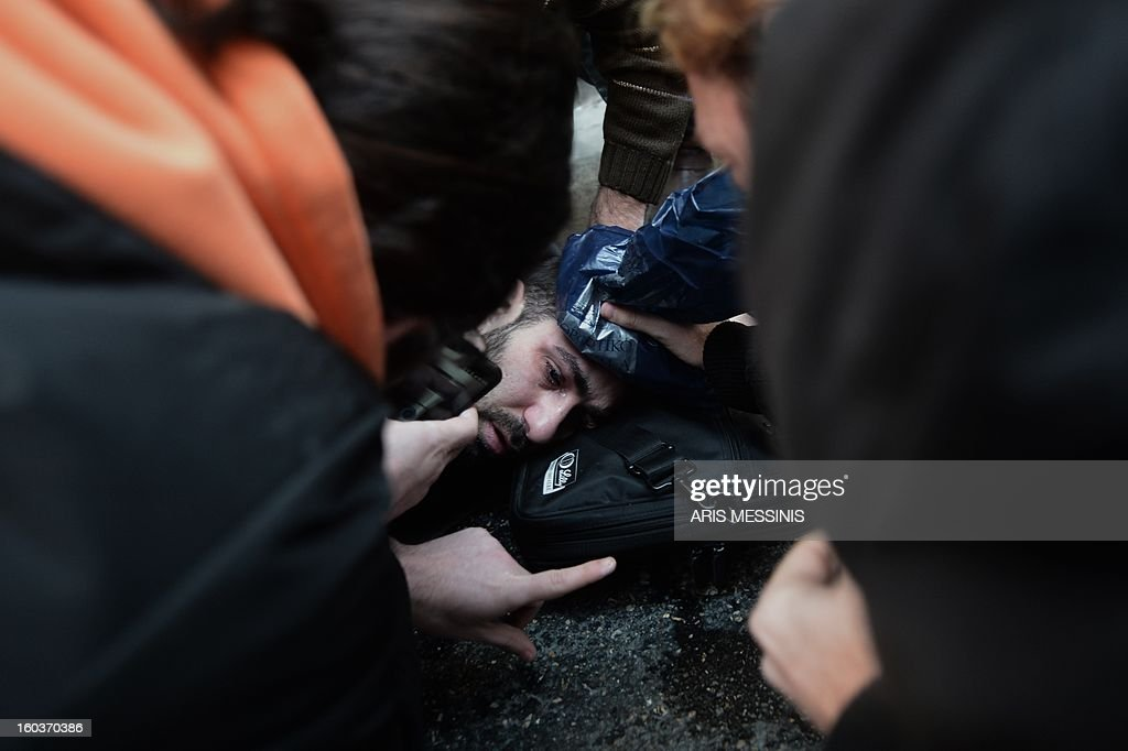 An injured protester receives treatment outside the Labour Ministry in Athens on January 30, 2013. Police were called in on Wednesday to dislodge around 30 Communist unionists from the labour ministry in a protest against new pension cut plans. The unionists were arrested and police used tear gas outside the building to disperse a larger group of protesters demanding their release. AFP PHOTO / ARIS MESSINIS