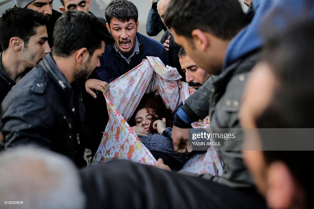 TOPSHOT - An injured protestor is carried by others during clashes between Turkish protestors and police as they demonstrate against curfews in eastern Turkey on February 14, 2016, in Istanbul. / AFP / YASIN AKGUL