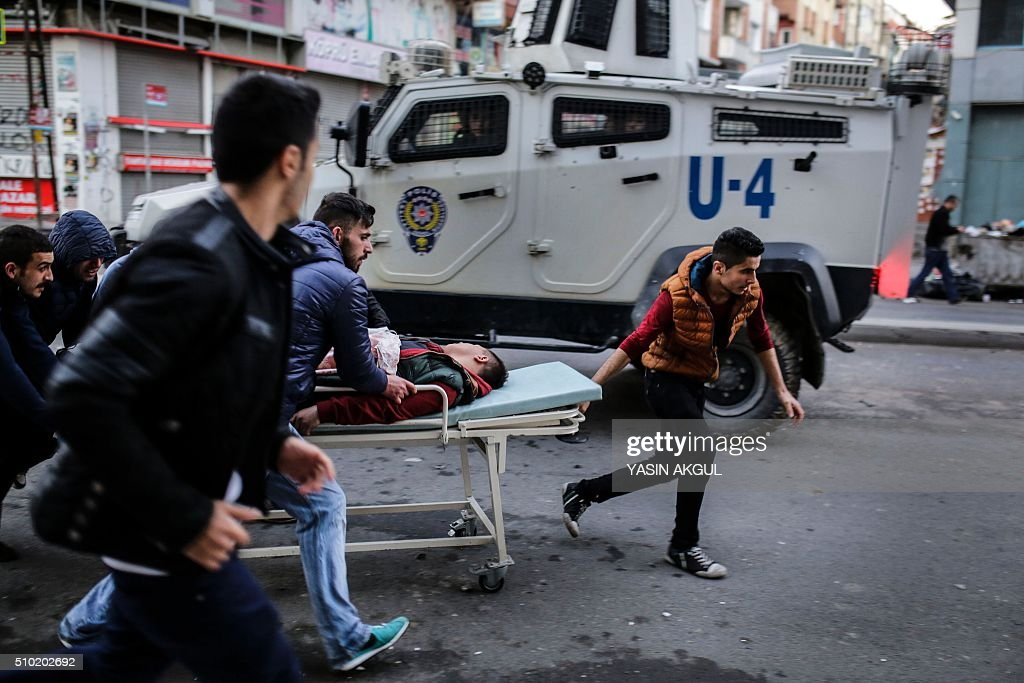 TOPSHOT An injured protestor is carried by others during clashes between Turkish protestors and police as they demonstrate against curfews in eastern...