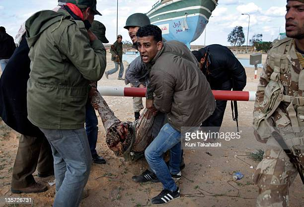 An injured rebel soldier fighting against Col Muammar Gaddafi is carried at the frontline March 9 2011 near Ras Lanuf Libya The government military...
