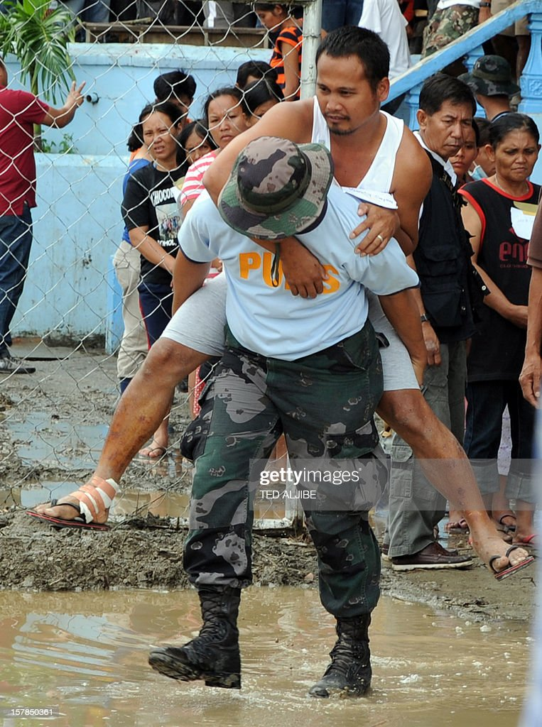 An injured resident is carried by a policeman to a location from where he will receive cash gift from Philippine President Benigno Aquino (not pictured) in New Bataan, Compostela Valley province on December 7, 2012. President Benigno Aquino vowed action on the Philippines' typhoon disasters December 7 as bruised and grieving survivors tried to recover from the latest that left nearly 500 people dead. AFP PHOTO/TED ALJIBE