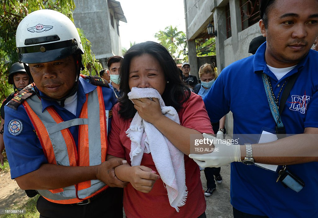 An injured resident (C) is helped by rescuers after a mortar shell believed to be from the Muslim rebels' position hit her house as government forces clash anew with remnants of Muslim rebels in Zamboanga City, on southern island of Mindanao on September 21, 2013. Philippine security forces killed eight Muslim rebels September 19, as they hunted the remnants of a guerrilla force hiding in homes of a major city and believed to be holding hostages. AFP PHOTO/TED ALJIBE