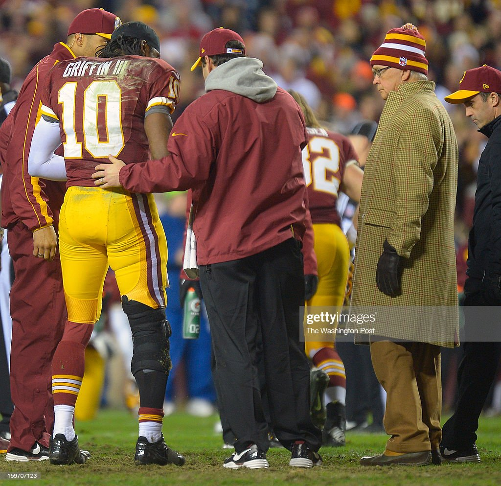 An injured Robert Griffin III (10) is helped up after a season ending injury in the 4th quarter to his right knee as Dr. James Andrews, right, looks on during the Washington Redskins loss the Seattle Seahawks in the first round of the NFC playoffs at FedEx Field in Landover MD, January 6, 2012 .
