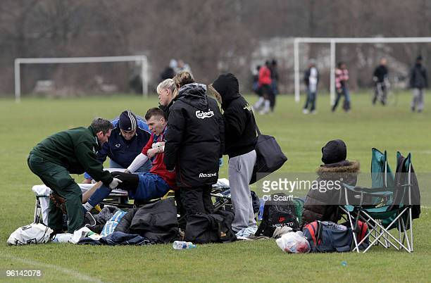 An injured Sunday League footballer for 'The Cock Tavern' is lifted onto a stretcher by paramedics during a match on the Hackney Marshes' pitches on...