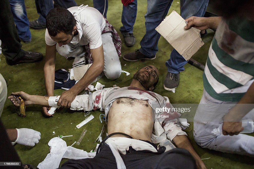 An injured supporter of deposed Egyptian President Mohammed Morsi is treated on the floor of the Fateh Mosque at Ramses Square on August 16, 2013 in Cairo, Egypt. Dozesns of people have been reported killed after heavy fighting between pro-Morsi protesters and Egyptian Security Forces broke out in central Cairo after pro-Morsi marches converged on downtown Cairo following midday prayer. Hundreds of pro-Morsi protesters were killed in Egypt's capital August 14, when Egyptian Security Forces undertook a planned operation to clear Morsi supporters from two sit-in demonstrations in Cairo. Egyptian Police and Army forces entered the protest sites in the Nasr City and Giza districts at dawn with tear gas, live fire and bulldozers. (Photo by Ed Giles/Getty Images).