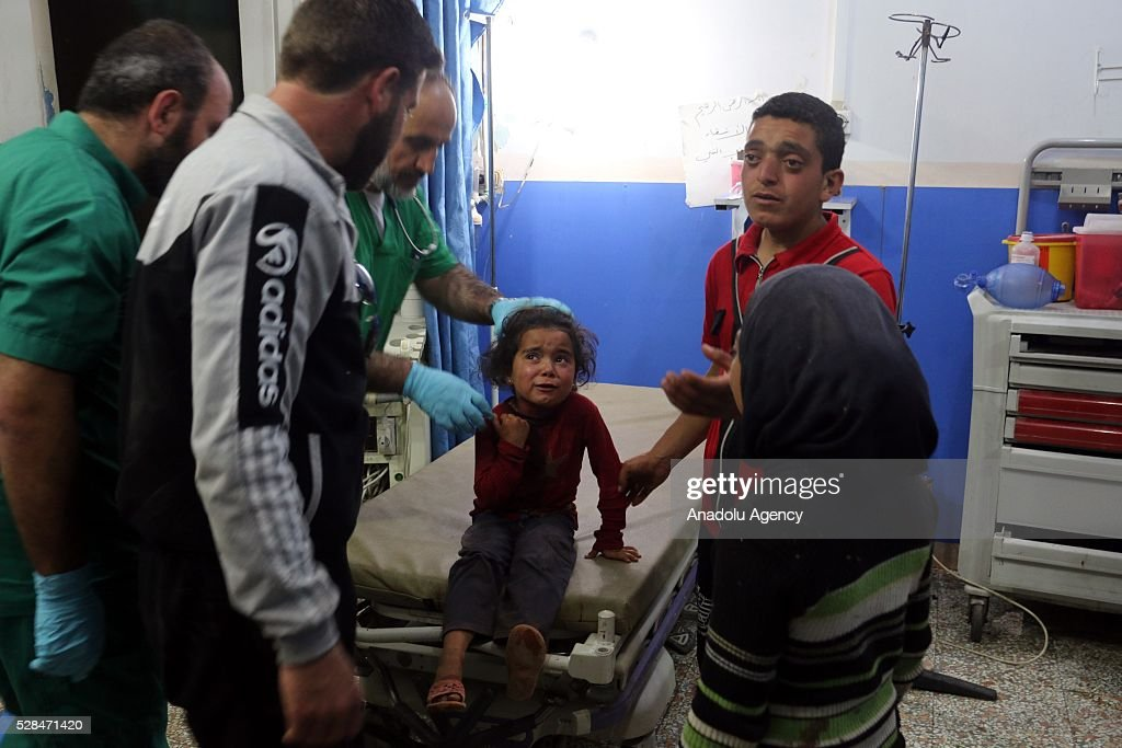 An injured Syrian child girl cries as she receives medical treatment at a field hospital after a Syrian regime warplane targeted the Kamuna refugee camp near the Syrian town of Sarmada town in the Idlib province after Syrian regime warplane targeted the camp on May 05, 2016. Eight people were killed and another 30 injured when a regime warplane targeted the Kamuna refugee camp.