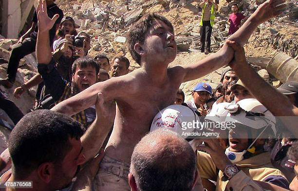 An injured Syrian kid is being evacuated from debris of a building after a vacuum bomb attack of Syrian army in the town of Selkin in Idlib Syria on...