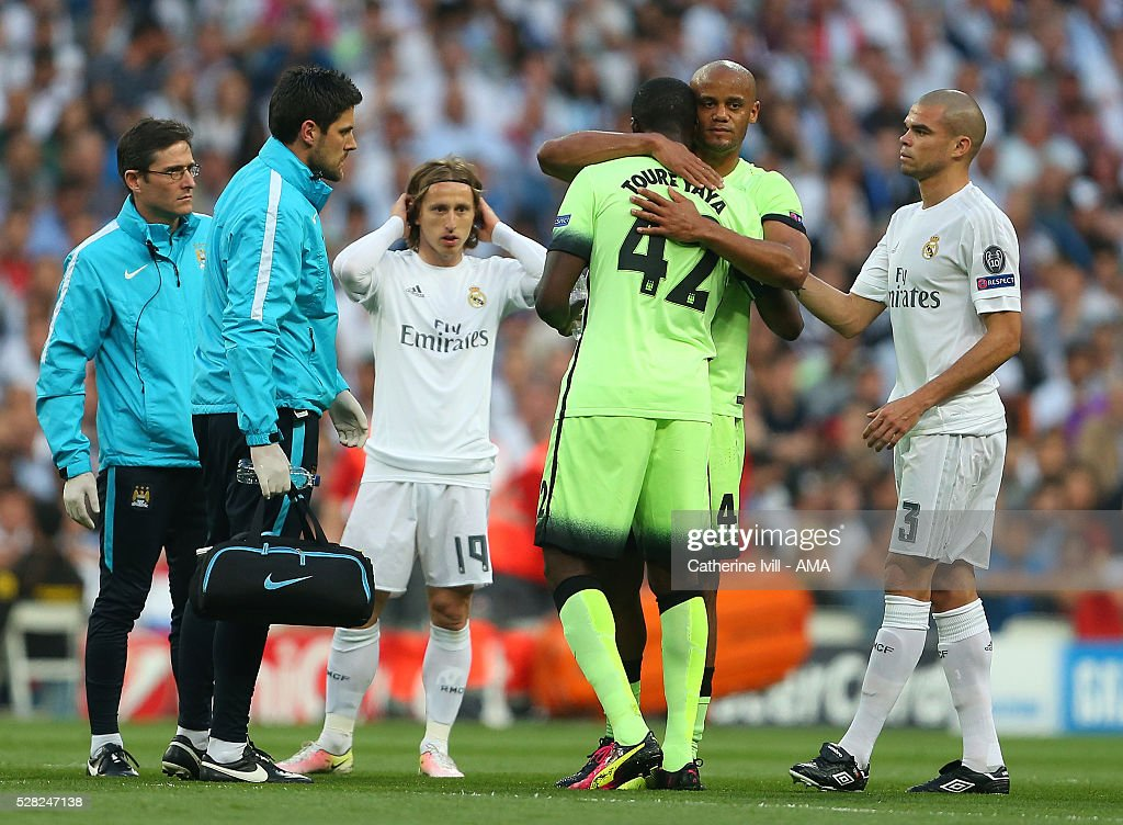 An injured <a gi-track='captionPersonalityLinkClicked' href=/galleries/search?phrase=Vincent+Kompany&family=editorial&specificpeople=504694 ng-click='$event.stopPropagation()'>Vincent Kompany</a> of Manchester City hugs Yaya Toure of Manchester City as he goes off during the UEFA Champions League Semi Final second leg match between Real Madrid and Manchester City FC at Estadio Santiago Bernabeu on May 4, 2016 in Madrid, Spain.