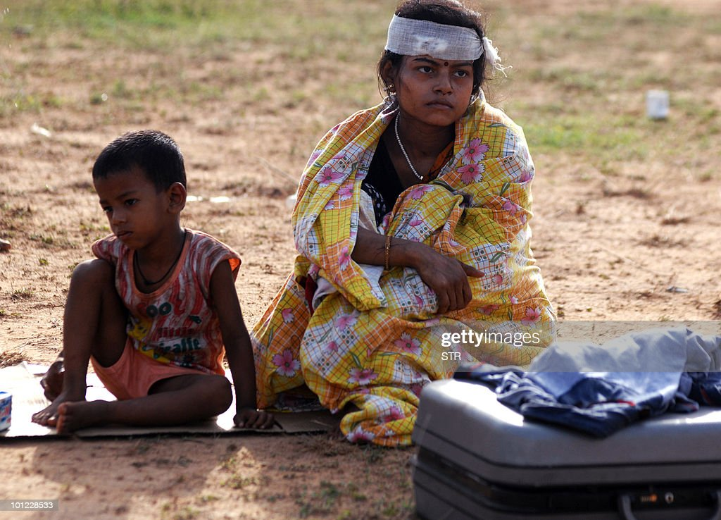 An injured woman and a child sit by the site of a fatal train collission in Sardiha some 135 km (85 miles) west of Kolkata on May 28, 2010. Maoist rebels derailed a high-speed train packed with sleeping passengers into the path of a freight train in eastern India Friday, killing at least 80 people, police said. It was the deadliest Maoist attack in recent memory and is likely to ramp up pressure on the government to consider calls for deploying the military in its fight against the rebels.
