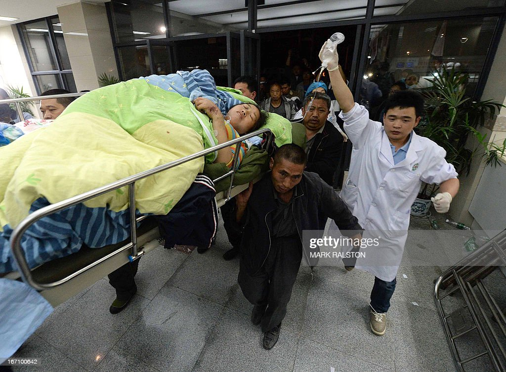 An injured woman is carried into Lushan People's hospital on a stretcher after a magnitude 7.0 earthquake hit Lushan county, Sichuan Province on April 20, 2013. More than 150 people were killed and 3,000 injured when an earthquake shook southwest China, wrecking homes and triggering landslides in an area devastated by a major tremor in 2008. AFP PHOTO / MARK RALSTON
