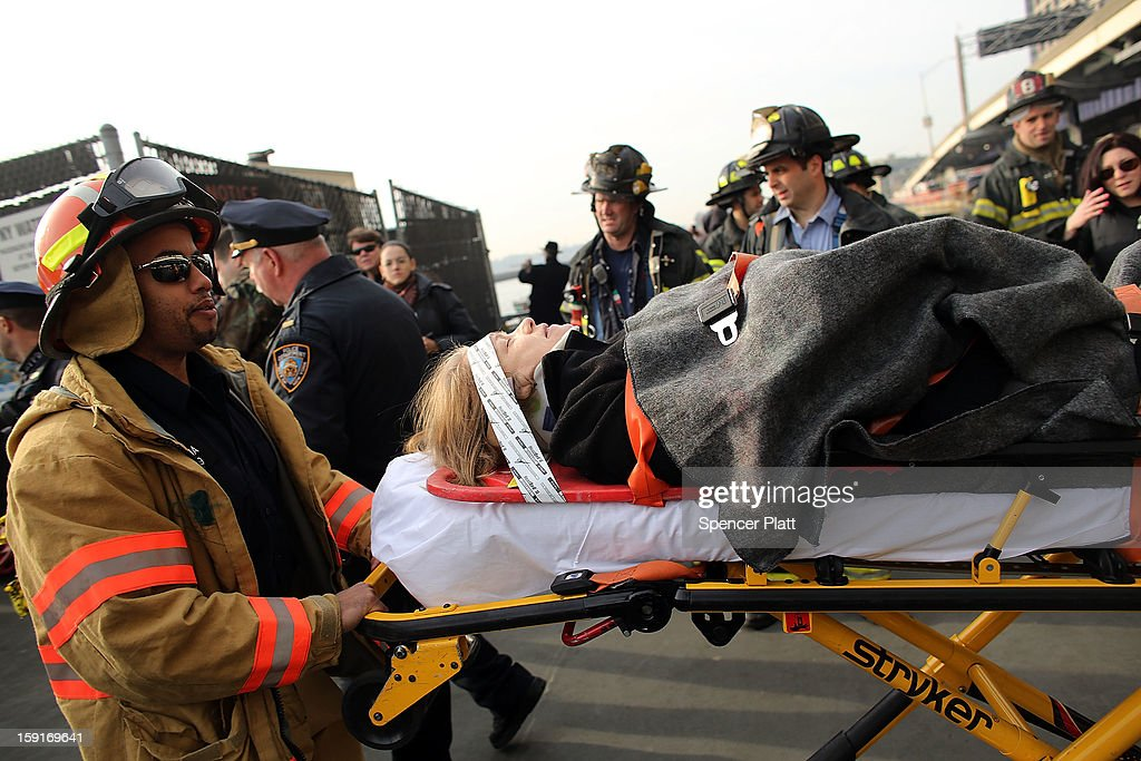 An injured woman is carried to a waiting ambulance following an early morning ferry accident during rush hour in Lower Manhattan on January 9, 2013 in New York City. About 50 people were injured in the accident, which left a large gash on the front side of the Seastreak ferry at Pier 11.