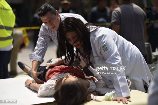 TOPSHOT An injured woman is helped after a powerful quake in Mexico City on September 19 2017 A powerful earthquake shook Mexico City on Tuesday...