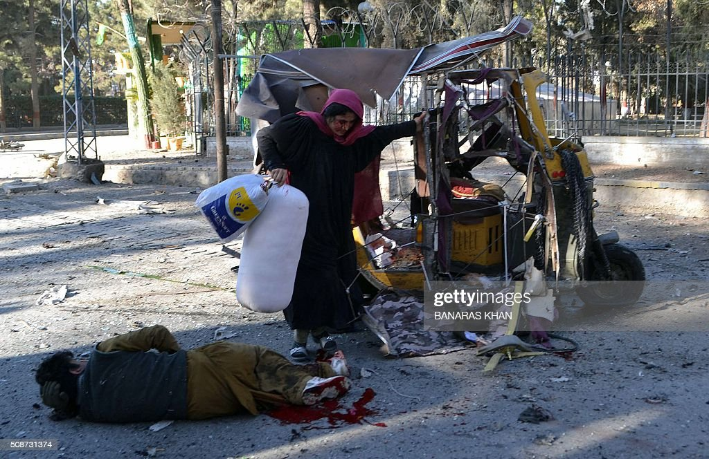 An injured women carries her belongings as she climbs out of a damaged auto rickshaw next to a blast victim at the site of a bomb explosion that targeted a security convoy in Quetta on February 6, 2016. A bomb blast struck a paramilitary vehicle and killed at least eight people and wounded more than 35 others in southwestern Pakistani city of Quetta, official said. AFP PHOTO / BANARAS KHAN / AFP / BANARAS KHAN