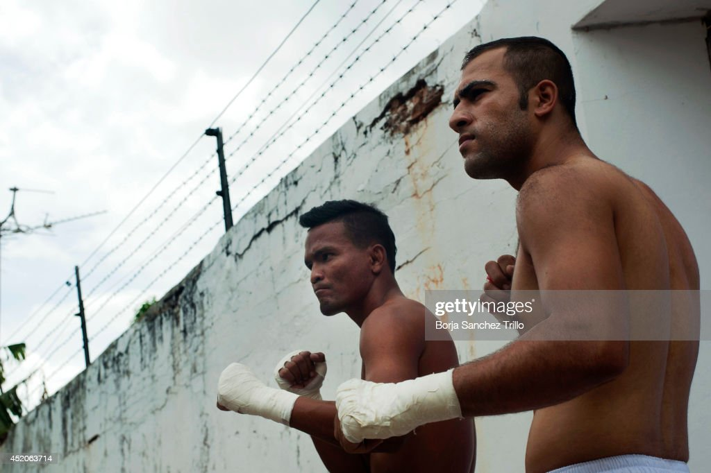 An inmate and a foreign fighter pose before their fight at Klong Pai prison on July 12, 2014 in Nakhon Ratchasima, Thailand. Prison Fight is an sport event which takes place in different prisons in Thailand and involves inmates fighting against foreign fighters looking for their rehabilitation, to promote the sport and good health among prisoners and to help them with better social adaptation for the future. Thailand has a strong tradition in fight sports such as Muay Thai and boxing, and inmates can reduce their jail sentence fighting in this event organized between World Prison Fight Association (WPFA) with the assistance of the Department Of Corrections.