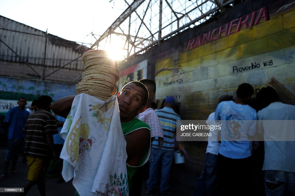 An inmate carries tortillas for breakfast at La Esperaza Jail in San Salvador, on November 23, 2012. La Esperanza, the largest jail in El Salvador, was designed to hold 800 inmates but currently holds 4700 prisoners. AFP PHOTO/Jose CABEZAS