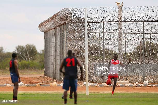 An Inmate from the Bombers Swans team kicks the ball as a camera keep watch behind a barbed wire fence during a Scratch Match at Alice Springs...