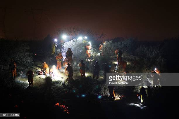 An inmate hand crew fights the North Fire which caused people to abandon their vehicles and flee as flames jumped the 215 freeway in the early...