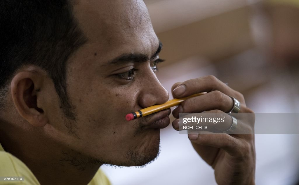 An inmate plays with his pencil after participating in the National Accreditation and Equivalency Examination, the alternative learning system, at the Manila City Jail in Manila on November 19, 2017. About 900 inmates, mostly have drug related cases, participate in the elemetary and highschool exam in the drive to educated the inmates. Some 900 inmates, mostly drug related cases, participated in the elementary and highschool exams in the drive to be educated.