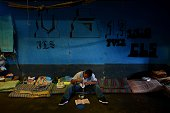 An inmate reads a book during his lunch hour at the Apanteos prison in Santa Ana 66 km west of San Salvador on July 15 2016 Apanteos is a model...