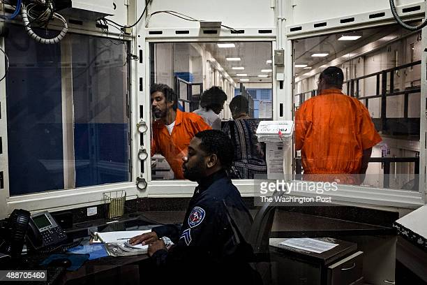 An inmate speaks through an intercom to a corrections officer as DC Mayor Muriel Bowser tours DC Central Jail after announcing policy changes to...