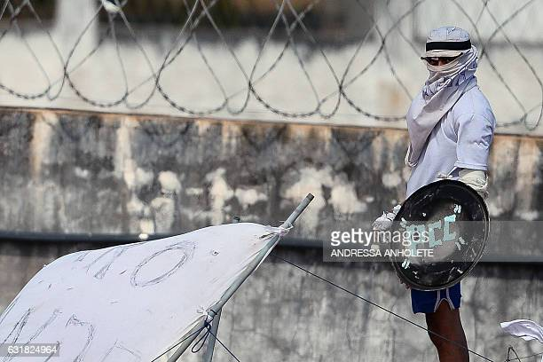 An inmate with his face covered stands on the prison roof during a rebellion in Alcacuz Penitentiary Center near Natal Rio Grande do Norte state...