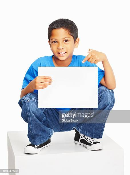 An innocent boy sitting on white cube  pointing at copyspace