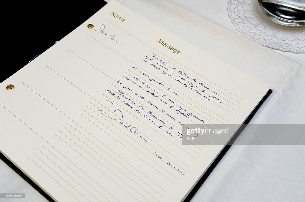 An inscription left by Britain's Prime Minister David Cameron is displayed in the book of condolence at the South African Embassy in central London on December 6, 2013 following the announcement of the death of the former South African leader Nelson Mandela who has died at the age of 95. British Prime Minister David Cameron said 'a great light had gone out' following Nelson Mandela's death as flags flew at half-mast at his Downing Street Office. 'Nelson Mandela was a towering figure in our time; a legend in life and now in death -- a true global hero,' said Cameron.