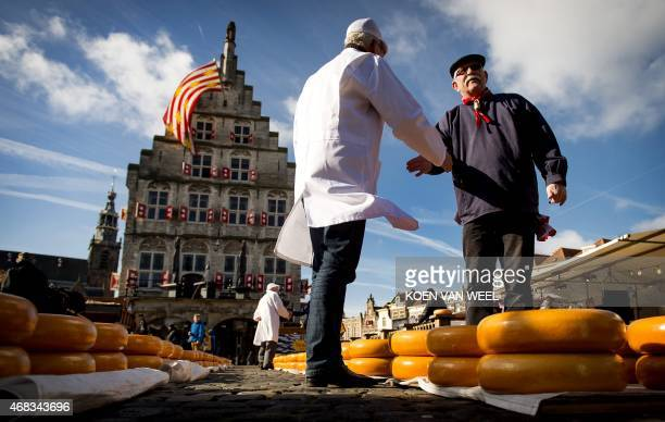 An Inspector speaks with a Cheesemaker at a market at the opening of the Dutch Cheese season in Gouda on April 2 2015 AFP PHOTO / ANP/ KOEN VAN WEEL...