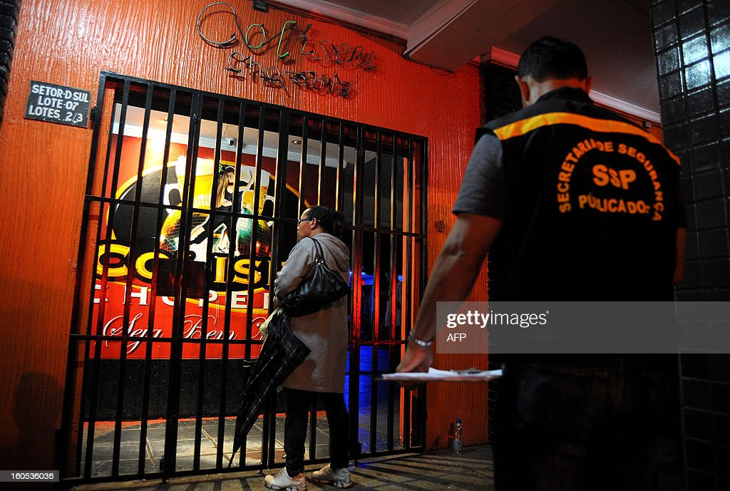 An inspector stands next to the entrance of a bar that was en closed because of an expired license in a suburb of Brasilia, on February 2, 2013. The Brazilian authorities ordered the inspection of many bars and nightclubs all over the country after the blaze in the Kiss Nightclub in Santa Maria, southern Brazil, that left more than 230 people dead. AFP PHOTO/ Pedro LADEIRA STR /pl/pa