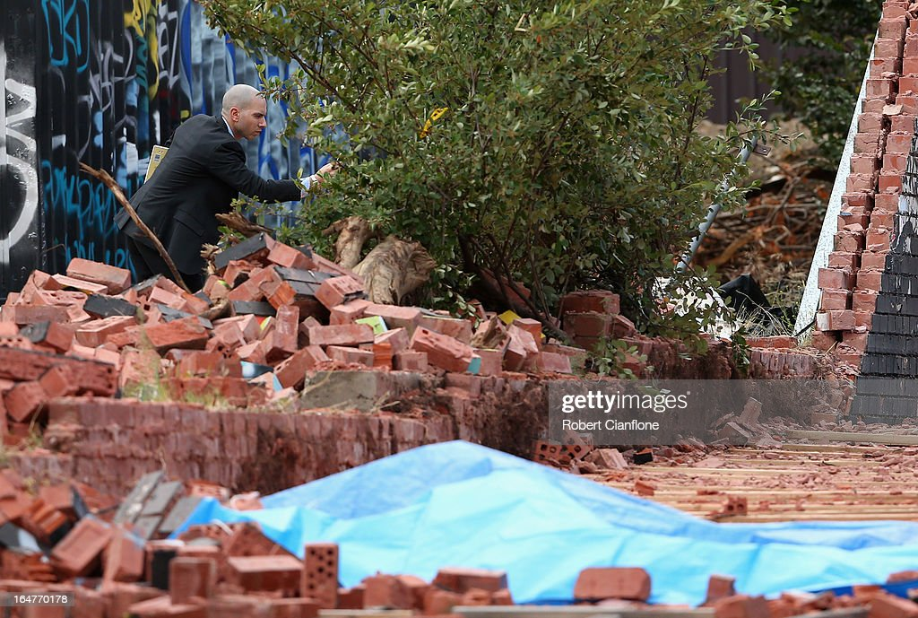 An inspector takes photographs of part of the wall that collapsed on March 28, 2013 in Melbourne, Australia. Police have confirmed two people have died and another has been seriously injured after a brick wall collapsed on Swanston street in Carlton in North Melbourne CBD.