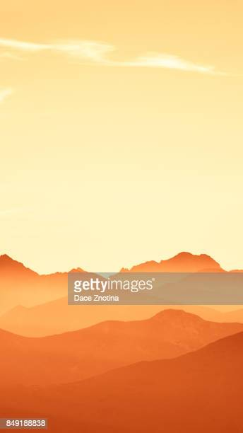 An inspiring mountain landscape in Tatry, Slovakia. Vivid, gradient scenery with perspective in red tone. Summer in mountains. Nature wallpaper in bright colors. A beautiful vertical wallpaper for a smartphone. Vertical image for a mobile use.