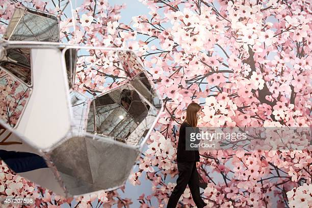 An installation by artist Tomas Saraceno entitled 'NGC 5892' is pictured as a woman talks on her phone next to an art work by Thomas Demand entitled...