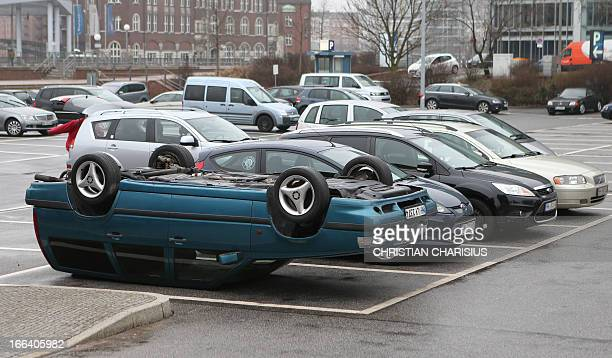 An installation by German artist HansPeter Feldmann a car laying upside down on a parking site is seen on April 12 2013 near the Deichtorhallen...