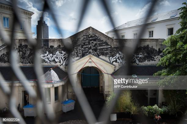 An installation entitled 'Entrez libre' by Pick Up Production in the former prison of Nantes is pictured through a fence on June 29 2017 during the...