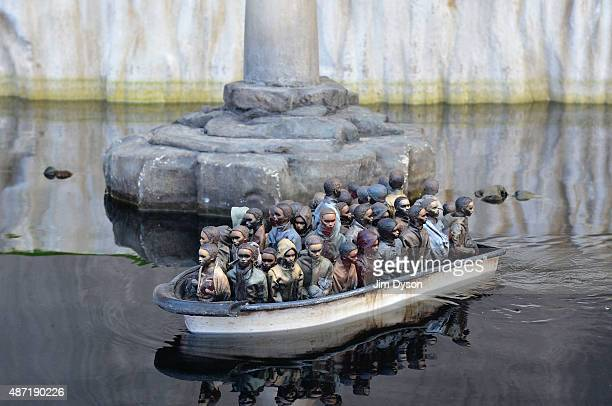 An installation of a boat pond featuring a remote controlled boat by Banksy depicts migrants at the white cliffs of Dover as Banksy's Dismaland...