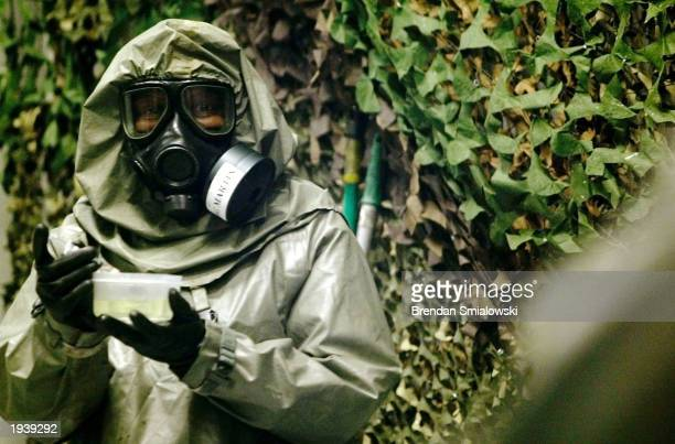 An instructor at the Fort Leonard Wood Chemical School who is designated as an agent handler carries the VX nerve agent to contaminate a jeep in one...