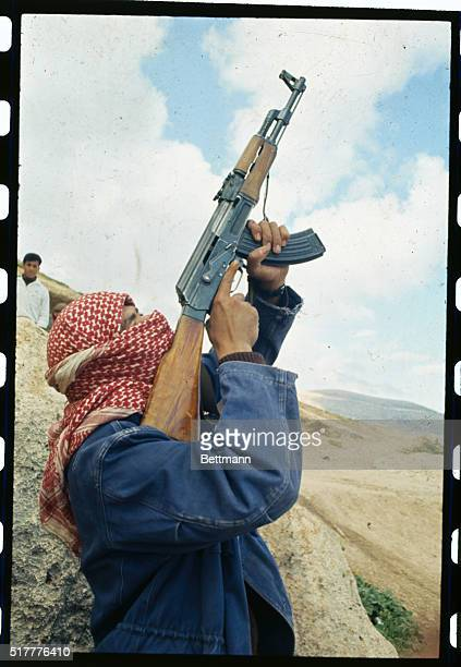An instructor fires a machine gun outside caves at Jarash in a recruits' training camp This is done to give the raw recruits a taste of what it is to...