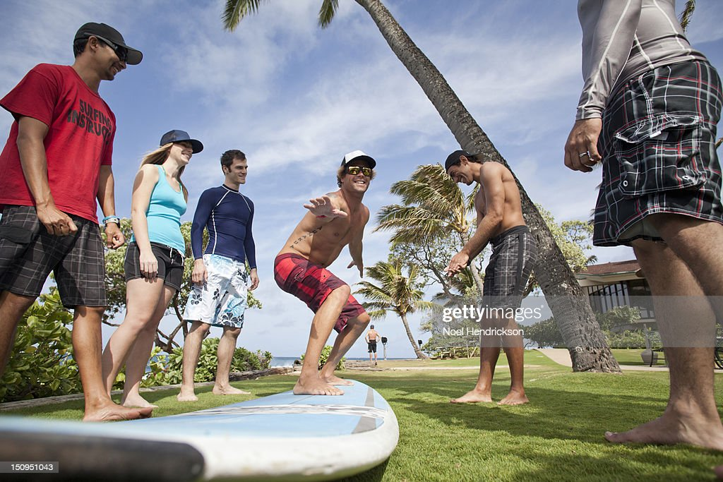 An instructor gives surf lessons by the ocean : Stock Photo