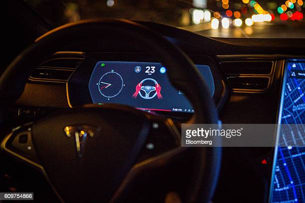 An instrument panel with the Tesla Motors Inc 80 software update displays an autopilot disengagement warning inside a Model S P90D vehicle in the...