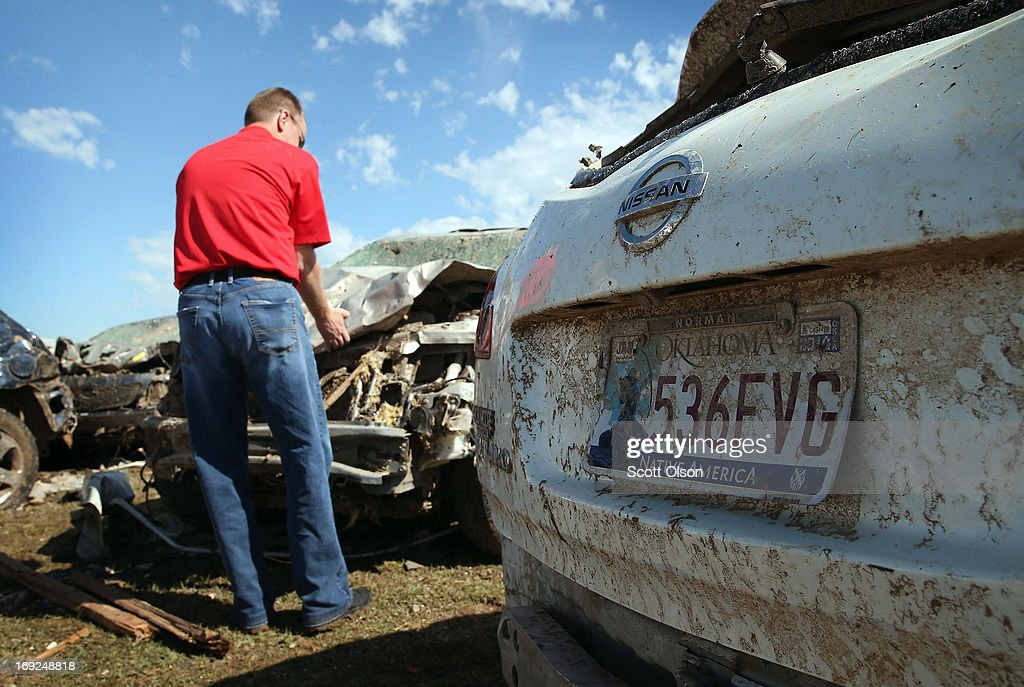 An insurance adjuster inspects damage to a vehicle along the I35 commercial strip after a tornado ripped through the area on May 22, 2013 in Moore, Oklahoma. The tornado of at least EF5 strength and two miles wide touched down May 20 killing at least 24 people and leaving behind extensive damage to homes and businesses. U.S. President Barack Obama promised federal aid to supplement state and local recovery efforts.