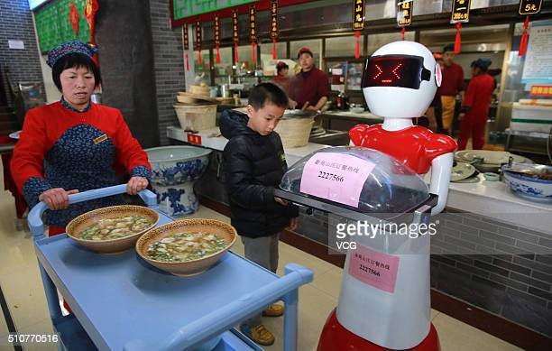 An intelligent robot delivers meals for customers at a farmhouse restaurant in Shanzhou District on February 16 2016 in Sanmenxa Henan Province of...