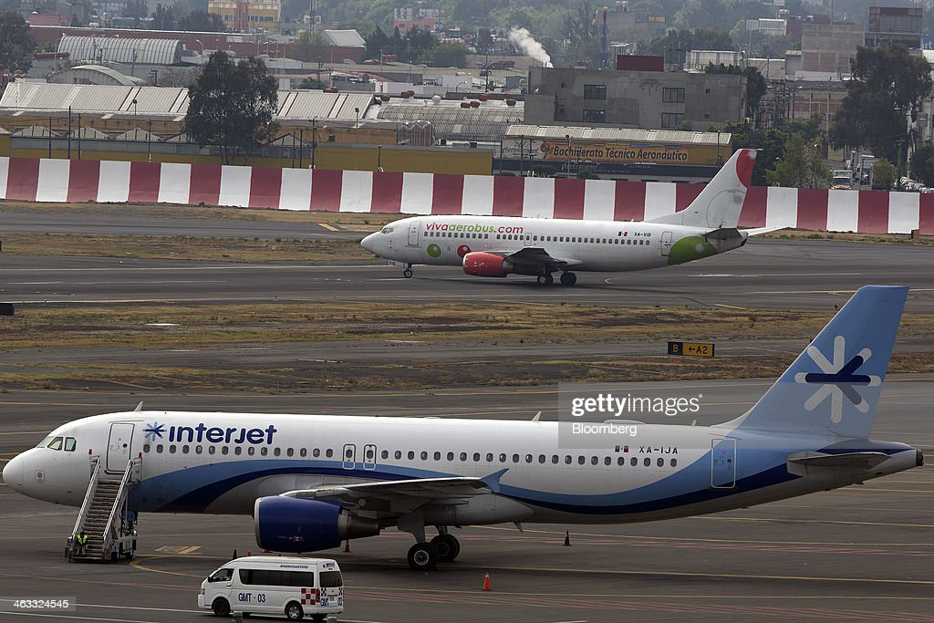 An Interjet airplane sits parked on the tarmac while a Grupo Viva Aerobus SAB airplane prepares to take off at Benito Juarez International Airport (AICM) in Mexico City, Mexico, on Thursday, Jan. 16, 2014. Grupo Viva Aerobus SAB filed for what would be Mexico's second initial public offering of shares by an airline since September as passenger traffic sets annual records. Interjet, Mexico's second-biggest carrier in 2012, may sell shares this year, Executive President Miguel Aleman Magnani said in November. Photographer: Susana Gonzalez/Bloomberg via Getty Images