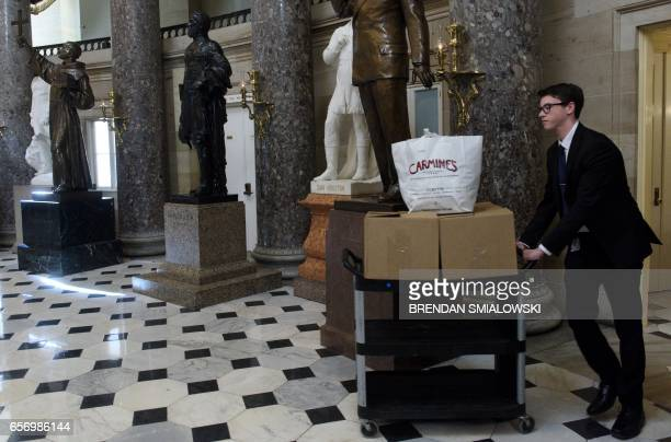 An intern brings food to members of the Freedom Caucus that are meeting after coming back from the White House where they met with US President...