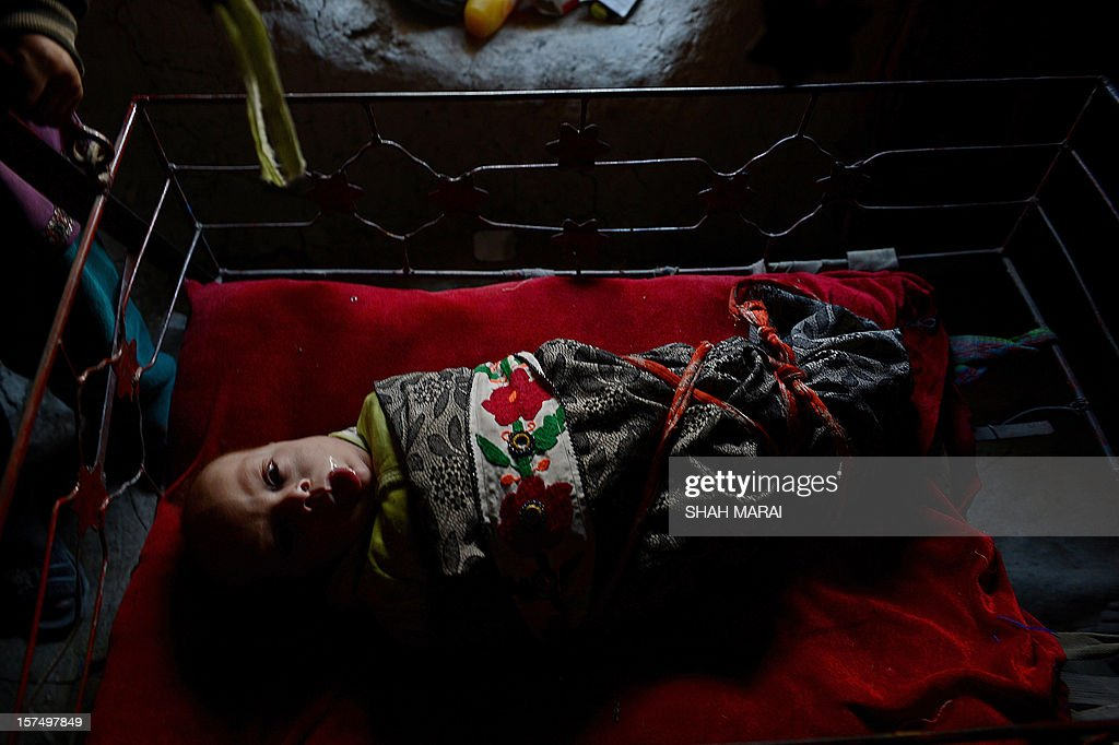 An internally displaced Afghan child rests in a cradle inside mud shelter in a makeshift camp as winter approaches in Kabul on December 4, 2012. The country has nearly half a million displaced people, many living in primitive camps where the cold weather will mean uncertainty for some. AFP PHOTO/SHAH Marai