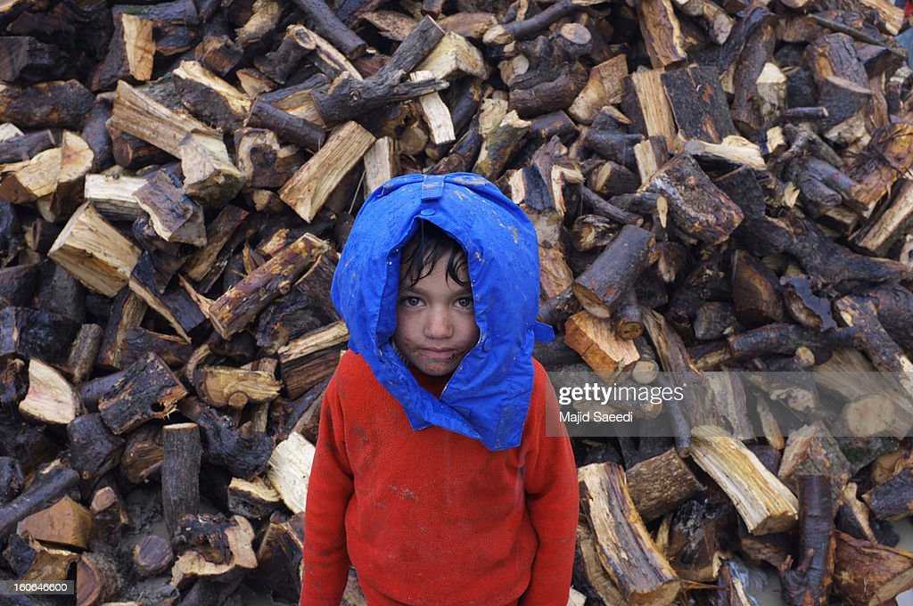An internally displaced Afghan child stands in front a wood pile, waiting to receive donations by Danish Refugee Council (DRC) at Chamand babrak Camp, on February 3, 2013 in Kabul, Afghanistan. According to the UN refugee agency, Afghanistan's internally displaced population has reached half a million, although the actual figure is believed to be much higher.