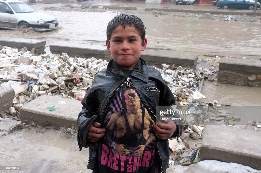 An internally displaced Afghan child stands in the rain, showing off his t-shirt featuring WWE wrestler Bret 'Hitman' Hart at Chamand babrak Camp, on February 3, 2013 in Kabul, Afghanistan. According to the UN refugee agency, Afghanistan's internally displaced population has reached half a million, although the actual figure is believed to be much higher.